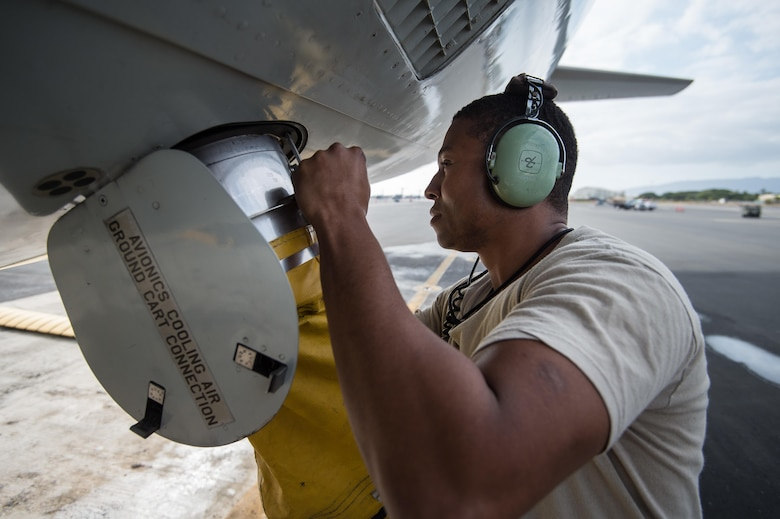Senior Airman Najee Menefee, a communications and navigation specialist from the 513th Aircraft Maintenance Squadron, hooks up a forced air hose to an E-3 Sentry Airborne Warning and Control System aircraft on Feb. 4 at Joint Base Pearl Harbor-Hickam, Hawaii. Reservists from the 513th Air Control Group deployed to the Hawaiian Islands to provide command and control for Sentry Aloha 17-01, a primarily Reserve and Air National Guard exercise that involves more than 40 aircraft and 1,000 personnel. (U.S. Air Force photo by 2nd Lt. Caleb Wanzer)
