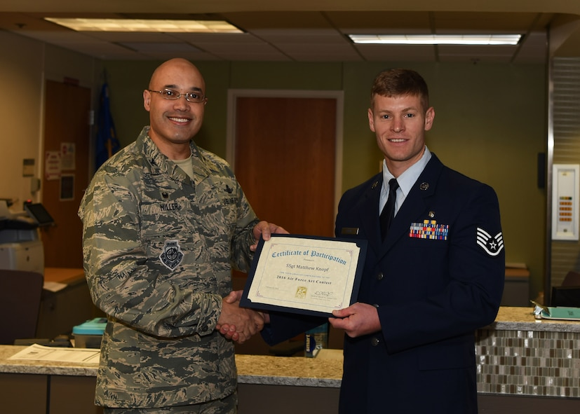 Col. David Miller Jr., 460th Space Wing commander, presents Staff Sgt. Matthew Knopf, 310th Aerospace Medical Flight health services management supervisor, with a certificate for his accomplishment of winning the 2016 Air Force Art Contest in the accomplished artist category Feb. 12, 2017, on Buckley Air Force Base, Colo. Knopf's painting was selected from a total of 326 entries in the adult accomplished artist category. (U.S. Air Force photo by Airman Holden S. Faul/ Released)