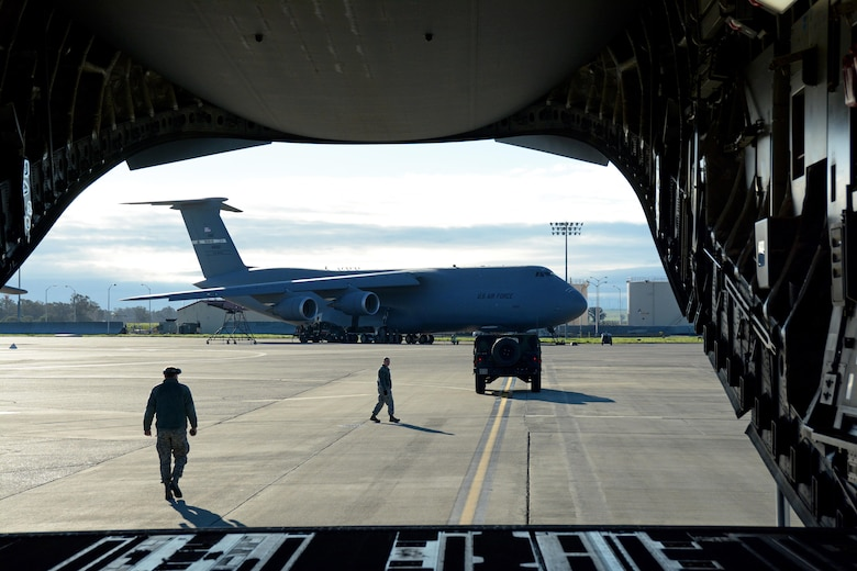 Citizen Airmen from the 55th Areoport Squadron guide a Humvee into place before it is backed into a C-17 Globemaster III prior to its take off from Travis Air Force Base, Calif., for Patriot Wyvern on Feb. 11, 2017. Patriot Wyvern is a hands-on, bi-annual event conducted by the 349th Air Mobility Wing designed to hone combat skills and improve organizational interoperability. (U.S. Air Force photo/Staff Sgt. Daniel Phelps)