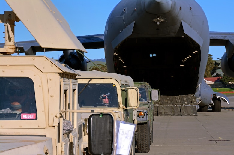Army Reserve Spec. James Williams, 801st Engineer Company horizontal engineer, awaits the go ahead for Humvees to be backed into a C-17 Globemaster III prior to its take off from Travis Air Force Base, Calif., for Patriot Wyvern on Feb. 11, 2017. Patriot Wyvern is a hands-on, bi-annual event conducted by the 349th Air Mobility Wing designed to hone combat skills and improve organizational interoperability. (U.S. Air Force photo/Staff Sgt. Daniel Phelps)