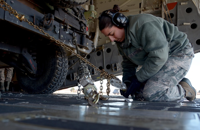 Senior Airman Christina Baeza, 55th Aeroport Squadron air transportation specialist, chains down a Humvee in a C-17 Globemaster III prior to its take off from Travis Air Force Base, Calif., for Patriot Wyvern on Feb. 11, 2017. Patriot Wyvern is a hands-on, bi-annual event conducted by the 349th Air Mobility Wing designed to hone combat skills and improve organizational interoperability. (U.S. Air Force photo/Staff Sgt. Daniel Phelps)