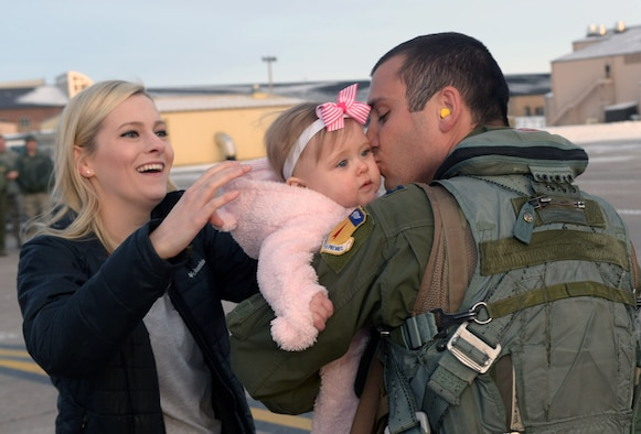 Capt. Alex, a pilot assigned to the 34th Expeditionary Bomb Squadron, reunites with his wife, Becky, and his daughter, Grace, at Ellsworth Air Force Base, S.D., Feb. 8, 2017, after his deployment to Guam, in support of the U.S. Pacific Command's Continuous Bomber Presence mission. Members of the 34th EBS flew a total of 242 sorties during the deployment. (U.S. Air Force photo by Airman 1st Class Donald C. Knechtel)
