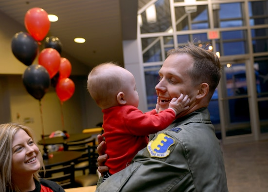 Capt. Chandler, a pilot assigned to the 34th Expeditionary Bomb Squadron, is welcomed home by his wife, Katelyn, and his son, John, at Ellsworth Air Force Base, S.D., Feb. 8, 2017. Approximately 300 Ellsworth Airmen deployed to Andersen Air Force Base, Guam, as part of the U.S. Pacific Command's Continuous Bomber Presence mission.  This forward deployed presence demonstrated the United States continuing commitment to stability and security in the Indo-Asia-Pacific region. (U.S. Air Force photo by Airman 1st Class Donald C. Knechtel)