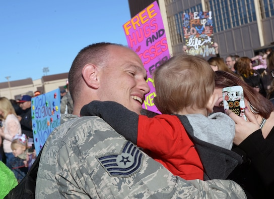 Tech. Sgt. Narley Wright, a weapons expediter assigned to the 28th Aircraft Maintenance Squadron, reunites with his family at Ellsworth Air Force Base, S.D., Feb. 12, 2017. Approximately 300 Ellsworth Airmen deployed to Andersen Air Force Base, Guam, as part of the U.S. Pacific Command's Continuous Bomber Presence mission. (U.S. Air Force photo by Airman 1st Class Donald C. Knechtel)