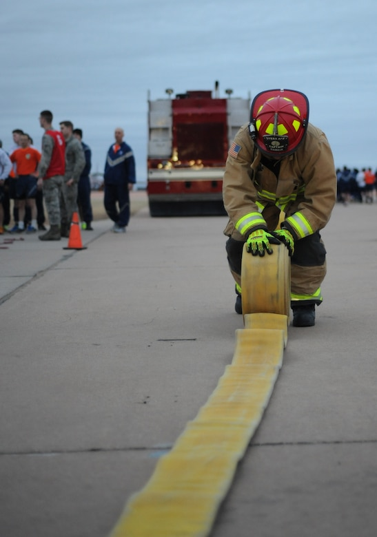 Martin Garcia, the 7th Civil Engineer Squadron lead firefighter, rolls up a fire hose during the Ray Rangel Remembrance Muster Feb. 13, 2017, at Dyess Air Force Base, Texas. Dyess Airmen participated in a firefighter geared workout to challenge the physical strength and endurance that is used during an emergency. (U.S. Air Force photo by Airman 1st Class Emily Copeland)
