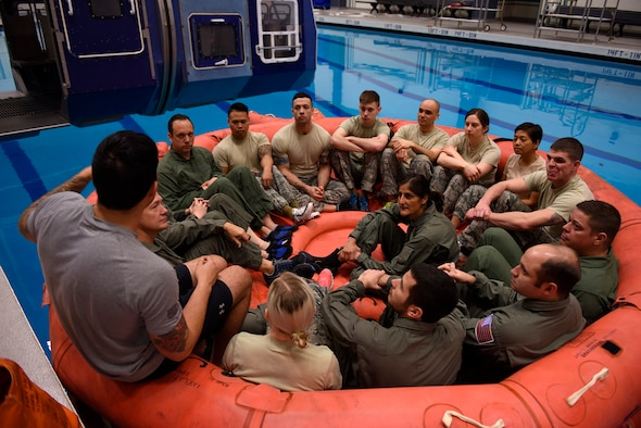 Four NASA astronauts sit in with a class of Survival School students being briefed on life raft procedures Feb. 10, 2017, at Fairchild Air Force Base, Wash. Water survival training is hosted by the base Fitness Center pool facilities. (U.S. Air Force photo/ Airman 1st Class Ryan Lackey)