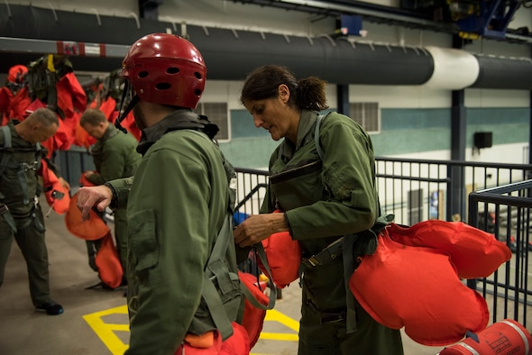 Sunita Williams, NASA astronaut, helps a fellow crew member suit up in preparation for water survival training Feb. 10, 2017, at Fairchild Air Force Base, Wash. The Survival School is the only military unit solely dedicated to survival and rescue training. (U.S. Air Force photo/ Airman 1st Class Ryan Lackey)