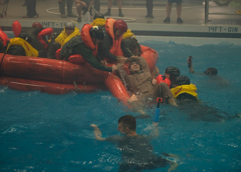 NASA astronauts and Survival School students help pull survivors into a life raft during a simulation Feb. 10, 2017, at Fairchild Air Force Base, Wash. Water survival instructors are hands on teachers, jumping into the action alongside their students. (U.S. Air Force photo/ Airman 1st Class Ryan Lackey)
