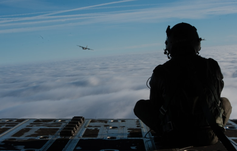 Airman 1st Class Quinn Harris, 37th Airlift Squadron loadmaster, peers over the skies at another C-130J Super Hercules flying over a blanket of clouds in Germany Feb. 10, 2017. During the Korean War, the squadron flew airborne assaults at Sukchon and Munsan-ni and aerial transportation between Japan and Korea. (U.S. Air Force photo by Senior Airman Lane T. Plummer)