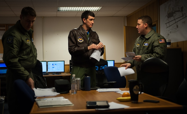 Lt. Col. Ryan Chmielewski, 37th Airlift Squadron director of operations, coordinates with Capt. Kenneth Jubb, 37th AS pilot, on their unit's 75th anniversary flight at Ramstein Air Base, Germany, Feb. 10, 2017. 37th AS pilots took to the skies to honor all those before them who have worn the unit patch. (U.S. Air Force photo by Senior Airman Lane T. Plummer)
