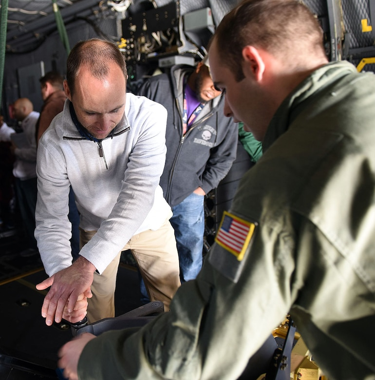 Todd Sanders, 568th Electronics Maintenance Group industrial engineering technician, left, receives a lesson from Staff Sgt. Mason Wise, Air Force Special  Operations aerial gunner, on how the weapons on an AC-130 Whiskey Gunship are operated. (U.S. Air Force photo by Tommie Horton)