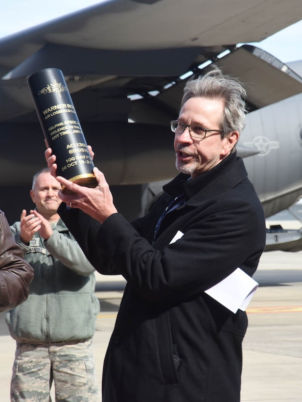 Doug Keene, WR-ALC  special assistant to the commander, holds up a 105mm round presented to the Warner Robins Air Logistics Complex from Maj. Gen. Haase on behalf of the 19,000 men and women who make up Air Force Special Operations Command. Haase was here to thank the workforce for the expedited work done on Special Ops aircraft over the course of the last year. (U.S. Air Force photo by Ed Aspera)