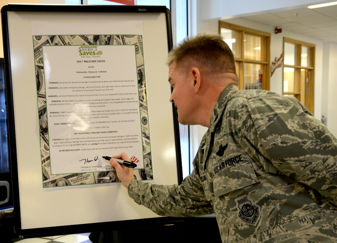 U.S. Air Force Col. Thomas Torkelson, 100th Air Refueling Wing commander, signs the 2017 Military Saves proclamation, Feb. 13, 2017, at the bowling center on RAF Mildenhall, England. Following the signing, Team Mildenhall personnel participated in a free scotch doubles bowling tournament hosted by the Airman and Family Readiness Center. Financial education classes are scheduled at both RAF Mildenhall and RAF Lakenheath Feb. 14 through March 3. (U.S. Air Force photo by Senior Airman Justine Rho)
