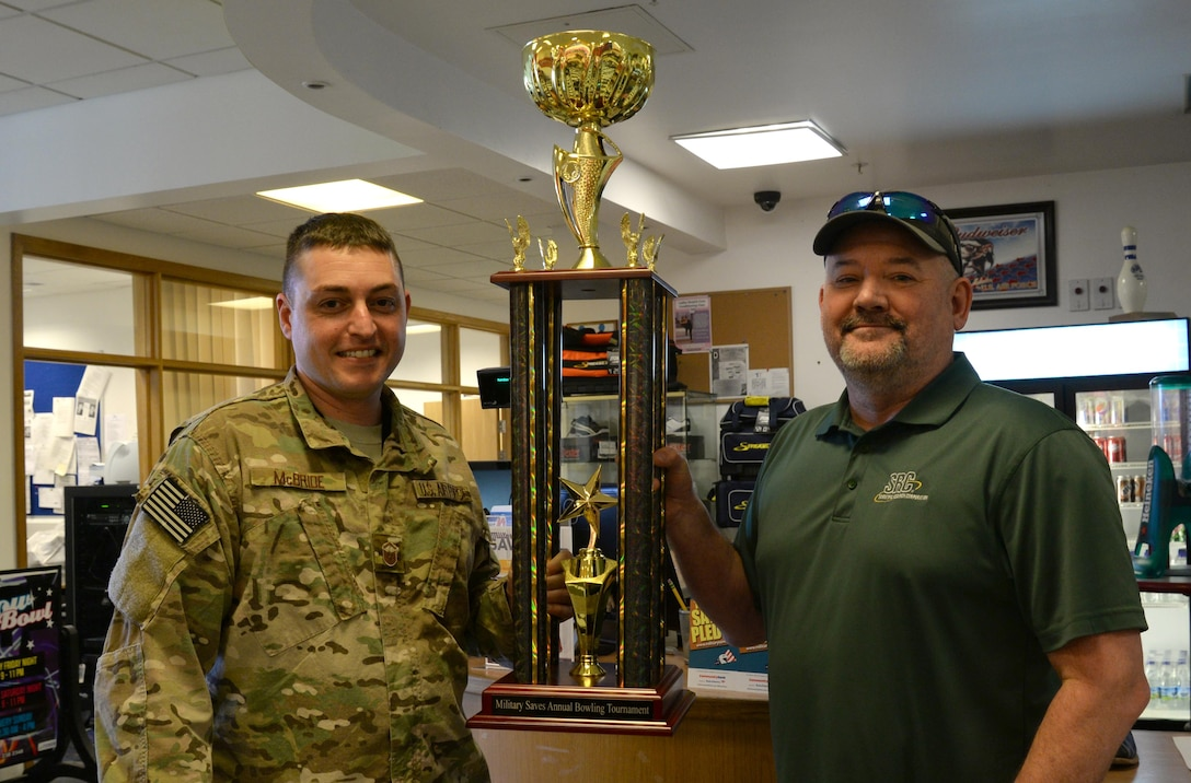 U.S. Air Force Master Sgt. Richard McBride, 25th Intelligence Squadron, Det. 2 flight chief, left, and Ricky Hoover, 25th IS, Det. 2 avionics technician, take home the Military Saves Scotch Bowling Tournament trophy, Feb. 13, 2017, at the bowling center on RAF Mildenhall, England. About 20 two-person teams competed in the free tournament. The event was hosted by the Airman and Family Readiness Center to promote Military Saves Week at both RAF Mildenhall and RAF Lakenheath. (U.S. Air Force photo by Senior Airman Justine Rho)