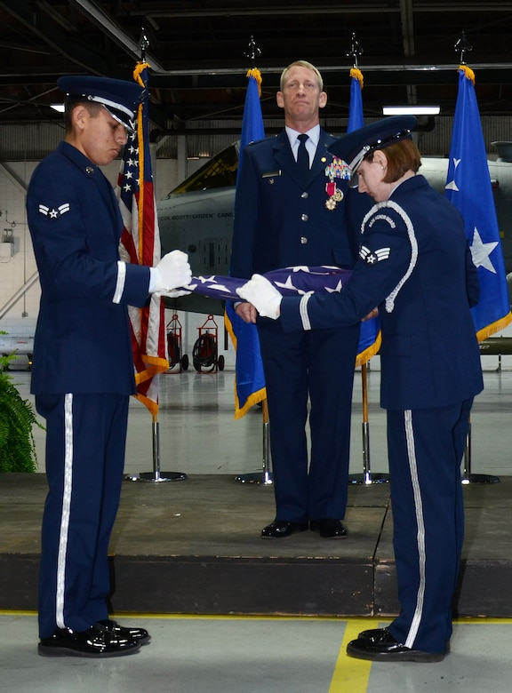 U.S. Air Force Col. Scott Caine (center), 9th Air Force vice commander, stands at attention Airman 1st Class Michael De La Cruz (left) and Senior Airman Caytlin Shreve (right), Shaw Air Force Base Honor Guard ceremonial guardsmen, fold the American Flag during Caine's retirement ceremony, Shaw AFB, S.C., Feb. 10, 2017. As part of the ceremony, the American Flag was displayed and refolded to show respect and gratitude toward those who have fought and continue to fight for freedom. (U.S. Air Force photo by Tech. Sgt. Amanda Dick)