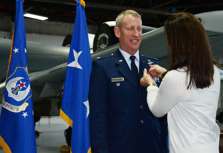 U.S. Air Force Col. Scott Caine, 9th Air Force vice commander, stands as his wife, Pam Caine, pushes in his retirement pin, Shaw Air Force Base, S.C., Feb. 10, 2017. Caine retired after 30 years in the Air Force and served in various positions throughout his career such as an aircraft maintenance officer, an A/OA-10 instructor, evaluator and pilot, and an operations officer. (U.S. Air Force photo by Tech. Sgt. Amanda Dick)