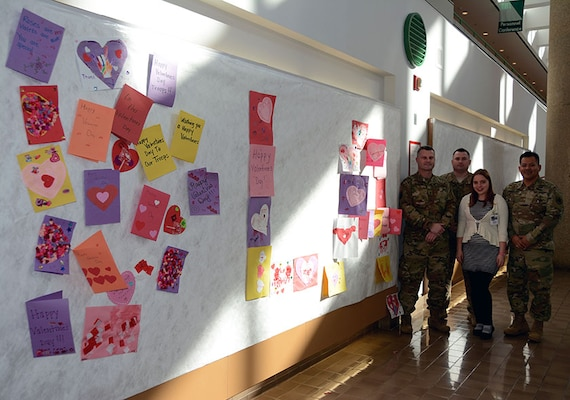 Defense Logistics Agency Aviation military members Chief Warrant Officer 4 Kevin Ryan, Chief Warrant Officer 3 Michael Jackson and Army Maj. Alex Shimabukuro from Defense Supply Center Richmond hung valentines cards, made by children at the Betty Ackerman-Cobb Child Development Center on DSCR, along the walls from the atrium for veterans to enjoy with Anne McLaughlin from Voluntary Service Feb. 10 2017 at Hunter Holmes McGuire Veterans Administration Medical Center. The valentines for veterans will be on display through the month in support to the Veterans Administration's annual Salute to Veterans.
