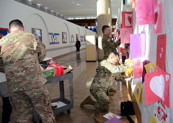 Defense Logistics Agency Aviation military members (left to right) Chief Warrant Officer 3 Michael Jackson, Army Maj. Alex Shimabukuro, Chief Warrant Officer 4 Kevin Ryan and from Defense Supply Center Richmond hung valentines cards, made by children at the Betty Ackerman-Cobb Child Development Center on DSCR, along the walls from the atrium for veterans to enjoy Feb. 10, 2017 at Hunter Holmes McGuire Veterans Administration Medical Center. The valentines for veterans will be on display through the month in support to the Veterans Administration's annual Salute to Veterans.