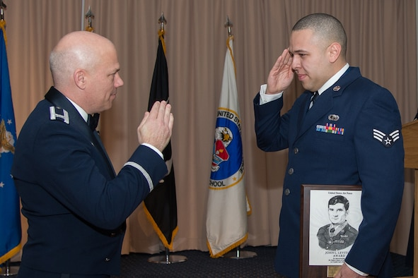 Senior Airman Michael Mejia salutes Col. Roman L. Hund, installation commander, after receiving the John L. Levitow Award during the Airman Leadership School graduation ceremony at the Minuteman Commons Feb. 10. Mejia, a member of the 66th Comptroller Squadron, received the award for achieving the highest overall standing from a combination of academic scores, performance evaluation and leadership qualities. It's the highest honor awarded to an enlisted PME student. (U.S. Air Force photo by Mark Herlihy)