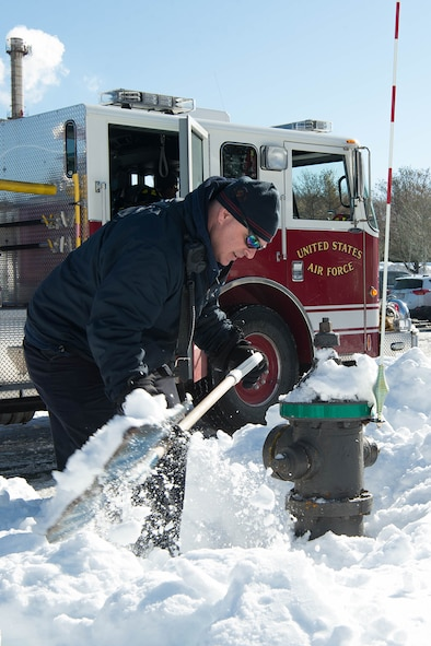 Lt. Dale Smith, a firefighter assigned to the 66th Civil Engineering Division, clears snow from around a fire hydrant on base Feb. 14. Smith and other firefighters were clearing snow-covered fire hydrants as part of winter fire safety following the recent snow storms. (U.S. Air Force photo by Jerry Saslav)