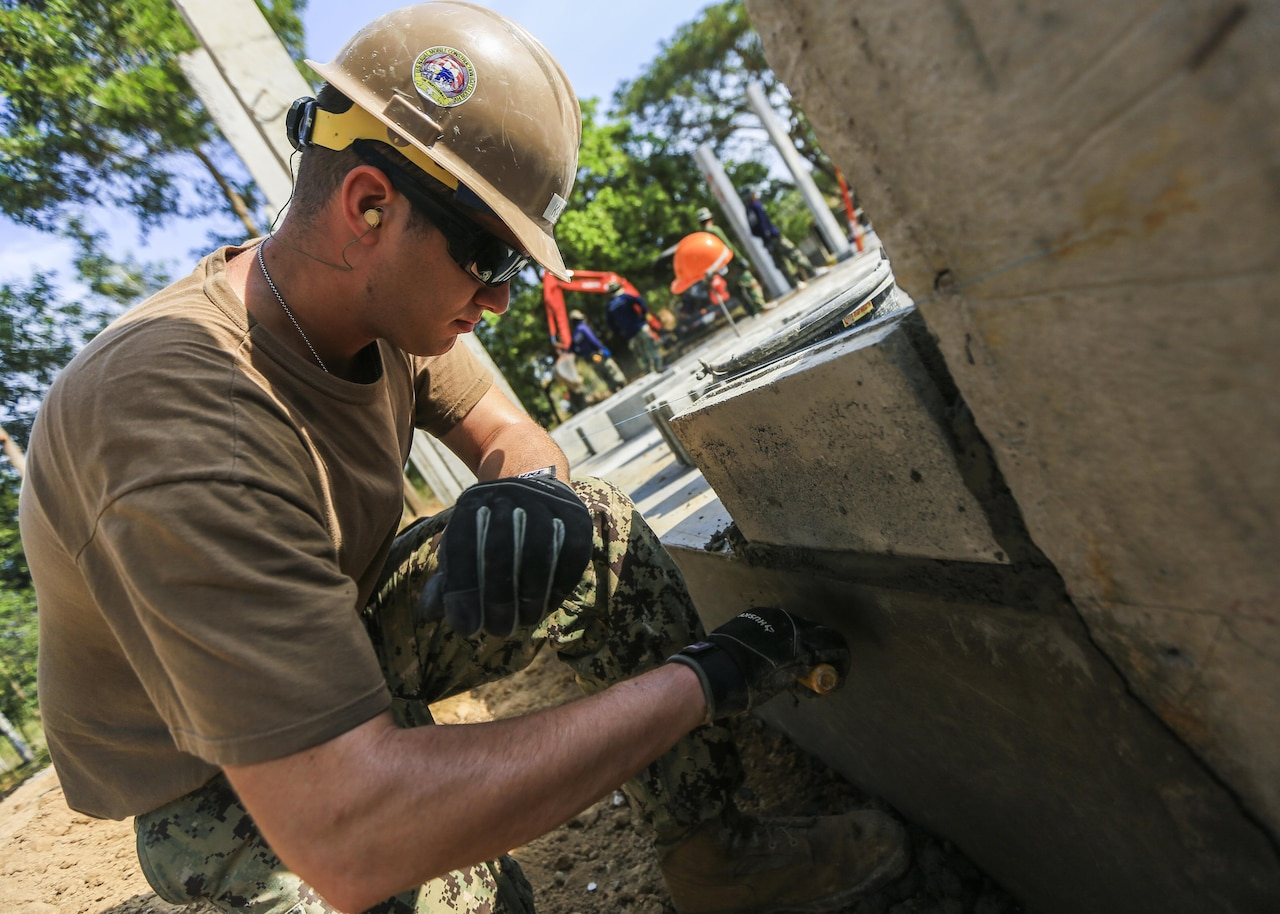 Navy Seaman Brandon Kase, a builder with Naval Mobile Construction Battalion 5, a Chicago native, spreads cement during the construction of a classroom at Ban Nong Mang School in Rayong, Thailand, during exercise Cobra Gold, Jan. 30, 2017. Marine Corps photo by Cpl. Wesley Timm