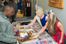 Rose Buckley, International Ms. 2017, and Elissa Troise-Greco, Mrs. Lewes Delaware America 2017, serve lunch to Team Dover Airmen and their families at the Teddy-Grams for Troops event Feb. 10, 2017, at the USO on Dover Air Force Base, Del. The food was donated by the Dover Mission BBQ. (U.S. Air Force photo by Mauricio Campino)