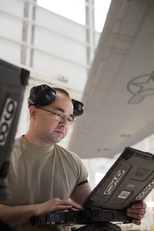 Senior Airman Brandon Mayfield (right), 945th Aircraft Maintenance Squadron crew chief, reviews a technical order for replacing C-17 Globemaster III engine panels, at Travis Air Force Base, Calif. Mayfield and Senior Airman Geoff Hayes (left), 945th AMXS guidance and control specialist, and Staff Sgt. Simon Nunez (center), 945th AMXS crew chief, worked together Feb. 10, 2017 during Wrench Week, which offers Citizen Airmen opportunities to reinforce and build their primary job skills. (U.S. Air Force photo by Ken Wright)