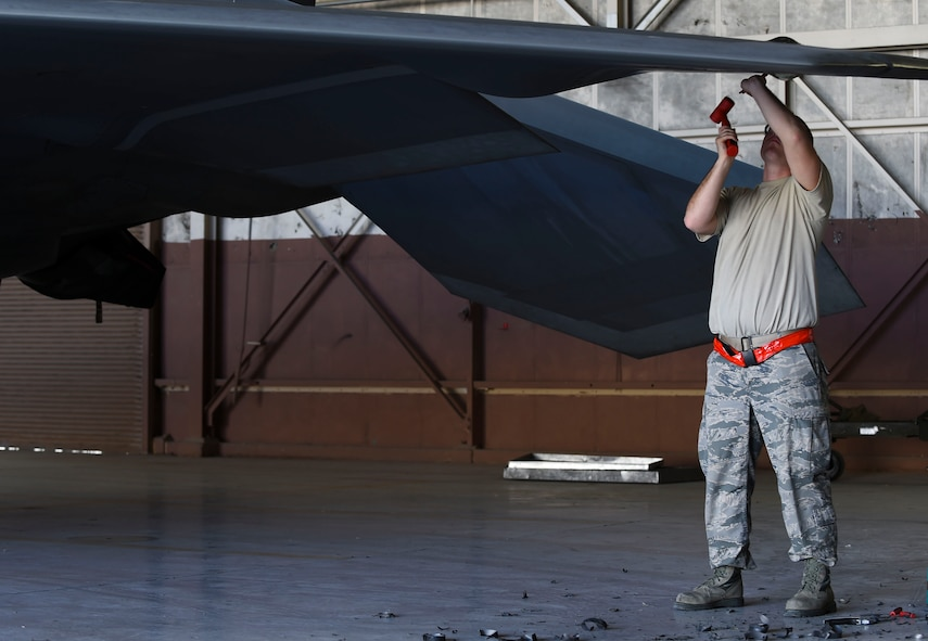 U.S. Air Force Staff Sgt. Zachary Dunn, 192nd Fighter Wing low observable aircraft structures technician, hammers radar absorbent material from an F-22 Raptor during Red Flag 17-1 at Nellis Air Force Base, Nev., Feb. 3, 2017. The material was covering a light panel that will later be fixed by  27th Aircraft Maintenance Unit maintainers. (U.S. Air Force photo by Staff Sgt. Natasha Stannard)