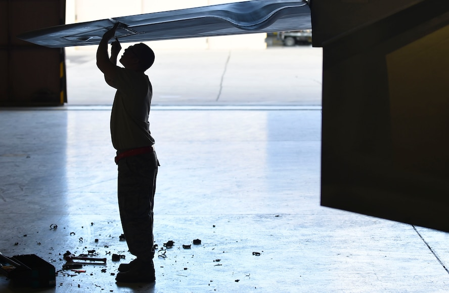 U.S. Air Force Staff Sgt. Zachary Dunn, 192nd Fighter Wing low observable aircraft structures technician, picks at radar absorbent material from an F-22 Raptor during Red Flag 17-1 at Nellis Air Force Base, Nev., Feb. 3, 2017. The absorbent material aids in the Raptor's low observability, a factor that makes it a stealth fighter aircraft. (U.S. Air Force photo by Staff Sgt. Natasha Stannard)