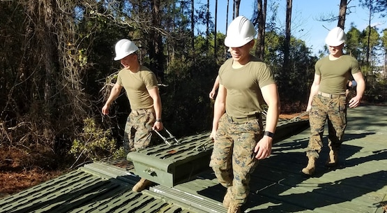 On February 8, 2017, Marines attached to Combat Engineer Officer course 2-17 (CEO 2-17) remove a ramp unit from a Medium Girder Bridge. During their period of instruction, CEO students learn how to plan for and construct a Medium Girder Bridge.  Pictured from left to right:  Second Lieutenants Carlos Perez, Manuel Ramirez, and Wesley Rathwick.