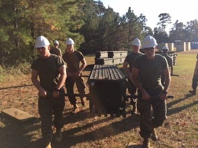 On November 16, 2016 Marines attached to Combat Engineer Officer course 1-17 (CEO1-17) use carrying bars to carry a top panel of a single story bridge. Medium Girder Bridges are built by connecting different pieces together while also slowly pushing the bridge across a gap. Pictured are Second Lieutenants Kristopher Satterwhite (Back Left), Taylor Hershberger (Back Right), Jacob Petersen (front left), and Oscar Machado (front right).