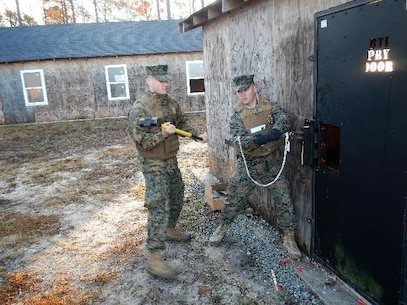 On December 15, 2016  Second Lieutenants Clark Kreitzer (left) and Taylor Hershberger (right), Marines attached to Combat Engineer Officer course 1-17 (CEO 1-17); practice mechanical breaching using a sledge hammer and hooligan tool to pry open a locked door. The hooligan tool is a multipurpose tool that is essential for mechanical breaching.