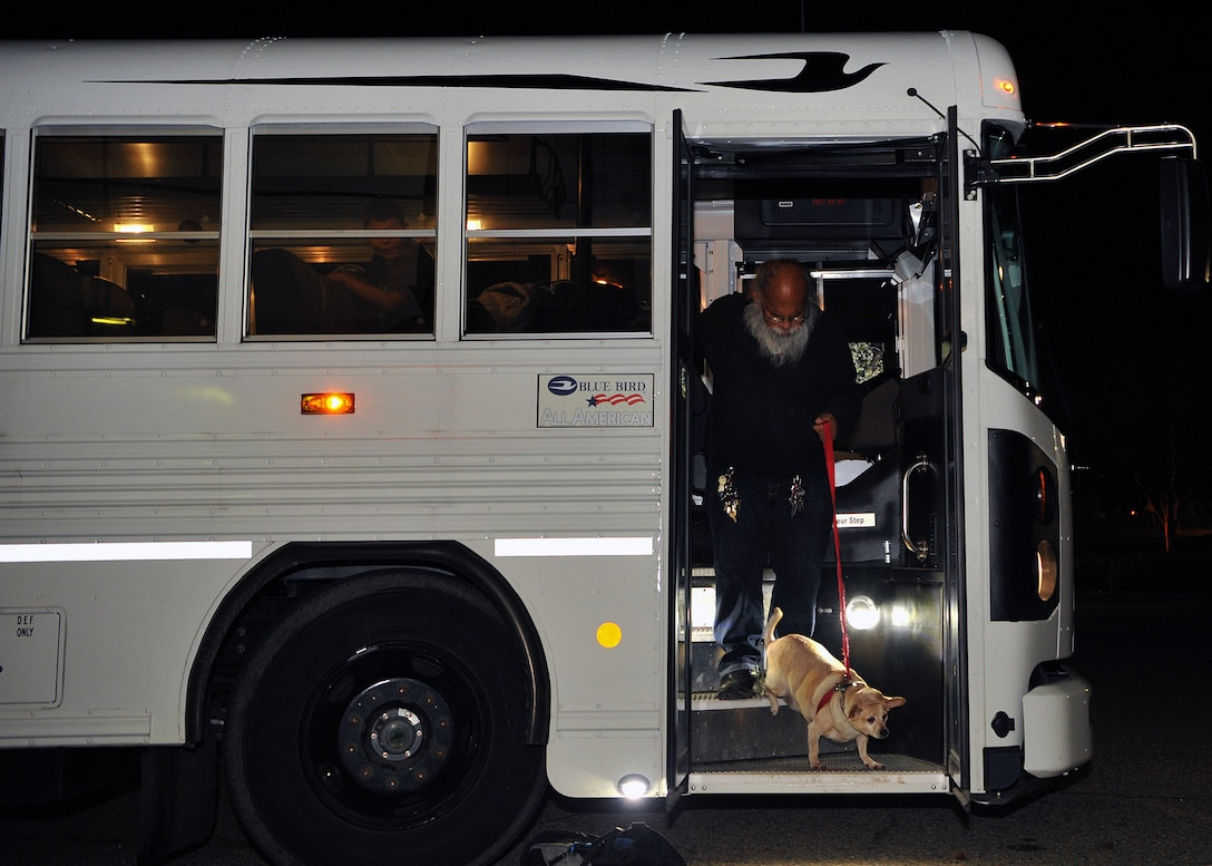 An evacuee and his dog exit a bus on Beale Air Force Base, California, during the Oroville spillway evacuation notice Feb. 13, 2017. Beale provided evacuees with shelter, food, and water. (U.S. Air Force photo/Airman Tristan D. Viglianco)