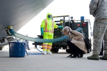 Sara Keller, Logistics, Engineering, Force Protection deputy director, Air Mobility Command, Scott Air Force Base, Ill., looks at the forward lavatory servicing connection of a C-5M Super Galaxy Feb. 8, 2017, at Dover Air Force Base, Del. Wearing protective gear, Airman 1st Class Benjamin Harper, 436th Aerial Port Squadron fleet service specialist, demonstrated for Keller how the lavatory service truck provides waste removal and servicing to C-5Ms, as well as other aircraft. (U.S. Air Force photo by Roland Balik)