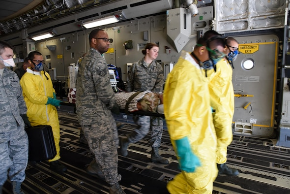 349th Aeromedical Staging Squadron Citizen Airmen litter carry simulated tuberculosis patients during a scenario for exercise Patriot Wyvern at Travis Air Force Base, Calif., Feb. 11, 2017. the 349th ASTS is responsible for the loading and unloading patients from aircraft and administering medical care. (U.S. Air Force photo by Senior Airman Sam Salopek)