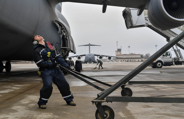 Senior Airman Earl Shelton, 721st Aircraft Maintenance Squadron aerospace maintenance technician, marshals a C-5M Super Galaxy into place at Ramstein Air Base, Germany, Jan. 24, 2017. After it was in place, 721st AMXS Airmen chocked the wheels, plugged it into a generator, checked tire pressure, refilled oil, and refueled the aircraft. On average, the 721st AMXS inspects, services, and repairs 30 aircraft in a single day, as part of the 521st Air Mobility Operations Wing at Ramstein.  (U.S. Air Force photo by Senior Airman Tryphena Mayhugh)