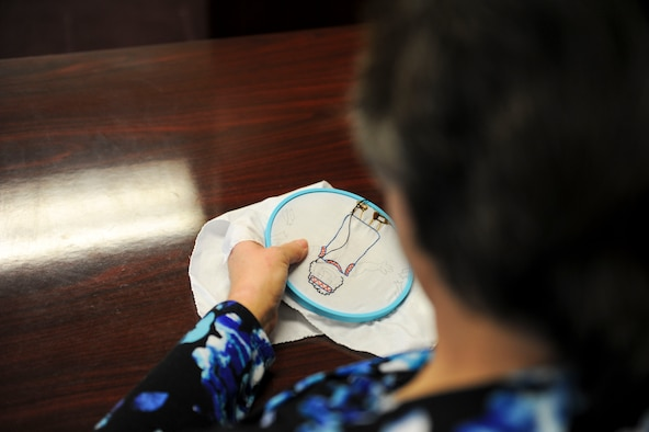 Department of the Air Force employee Kristina Anderson, a 354th Fighter Wing legal office receptionist secretary, embroiders a piece of a quilt Jan. 27, 2017, at Eielson Air Force Base, Alaska. Anderson has been sewing for approximately 45 years and usually spends her lunch breaks sewing gifts for her grandchildren. (U.S. Air Force photo by Airman Isaac Johnson)