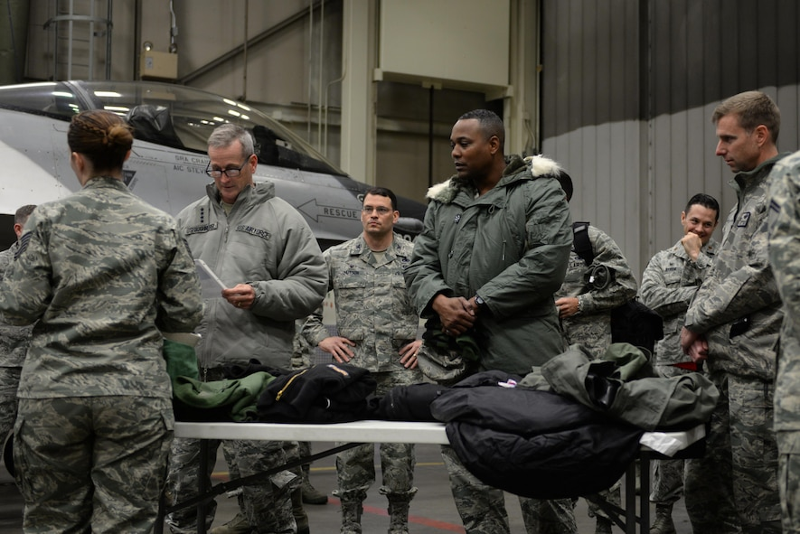 U.S. Air Force Gen. Terrence O'Shaughnessy, Pacific Air Forces commander, and Chief Master Sgt. Anthony Johnson, Pacific Air Forces command chief, receives a briefing about arctic flight suits by Tech. Sgt. Skye Perry, a 354th Operations Support Squadron aircrew flight equipment craftsman, during a base visit at Eielson Air Force Base, Alaska, Feb. 8, 2017. During the visit, O'Shaughnessy and Johnson met with Airmen across the base to gain a firsthand understanding of the unique challenges Alaska's environment offers and how Icemen thrive and survive. (U.S. Air Force photo by Airman 1st Class Cassandra Whitman)