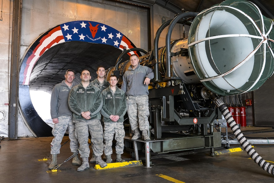 Air National Guardsmen from New Jersey's 177th Fighter Wing pose for a photo in front of the morale painting they designed, funded and created at the engine test cell facility, located at the 177th Fighter Wing, Atlantic City Air National Guard Base, N.J., on Jan. 31, 2017. The engine shop personnel, including two members not shown, wanted to create a feeling of Esprit de Corps and a reminder of just how amazing it is to work on such a complex and important military machine. The General Electric F110-GE-100 turbofan, prepped and ready for testing, produces close to 29,000 pounds of static thrust in afterburner, which can propel the Fighting Falcon to approximately twice the speed of sound. (U.S. Air National Guard photo by Master Sgt. Andrew J. Moseley/Released)