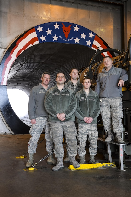 "Air National Guardsmen from New Jersey's 177th Fighter Wing pose for a photo in front of the morale painting they designed funded and created at the propulsion element ""hush house"", located at the 177th Fighter Wing, Atlantic City Air National Guard Base in Egg Harbor Township, N.J., on Jan. 31, 2017. The engine shop personnel, including two members not shown, wanted to create a feeling of esprit de corps and a reminder of just how amazing it is to work on such a complex and important military machine. The General Electric F110-GE-100 turbofan, prepped and ready for testing, produces close to 29,000 pounds of static thrust in afterburner, which can propel the Fighting Falcon to approximately twice the speed of sound. (U.S. Air National Guard photo by Master Sgt. Andrew J. Moseley/Released)"