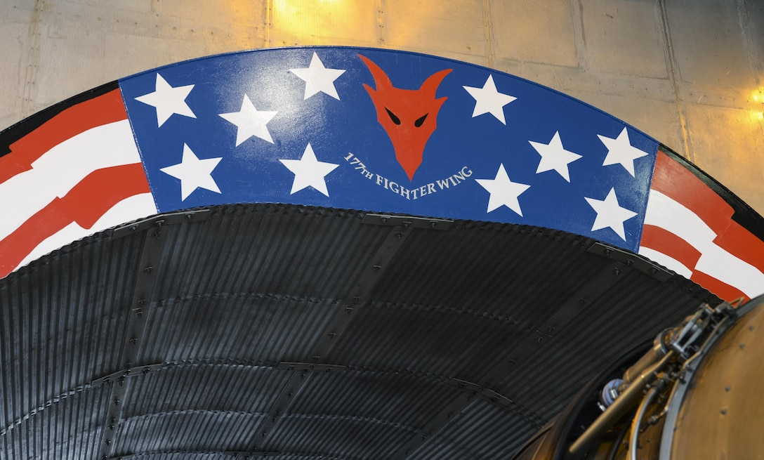 "An image of a morale painting designed, funded and created by members of a New Jersey Air National Guard propulsion element at the ""hush house, located at the 177th Fighter Wing, Atlantic City Air National Guard Base, N.J., on Jan. 31, 2017. The engine shop personnel wanted to create a feeling of Esprit de Corps and a reminder of just how amazing it is to work on such a complex and important military machine. The General Electric F110-GE-100 turbofan, prepped and ready for testing, produces close to 29,000 pounds of static thrust in afterburner, which can propel the Fighting Falcon to approximately twice the speed of sound. (U.S. Air National Guard photo by Master Sgt. Andrew J. Moseley/Released)"