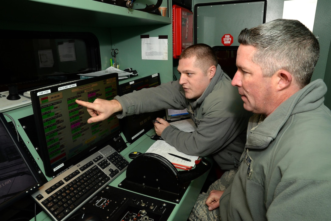"""U.S. Air Force Master Sgt. Andre Lazaro, engine test cell supervisor with the 177th Fighter Wing of the New Jersey Air National Guard, points to a fan rotor speed indicator while Tech. Sgt. Robert Taylor, propulsion mechanic, prepares to fire up an engine from an F-16C+ Fighting Falcon for testing at the propulsion shop's engine test cell facility located at the Atlantic City Air National Guard Base in Egg Harbor Township, N.J. on Jan. 31, 2017. The facility, also known as the """"Hush House"""", is a multi-function building that can be used to perform diagnostic, troubleshooting and follow-on maintenance testing of the General Electric F110-GE-100 turbofan, which produces close to 29,000 pounds of static thrust in afterburner and can propel the Fighting Falcon to approximately twice the speed of sound. (U.S. Air National Guard photo by Master Sgt. Andrew J. Moseley/Released)"""