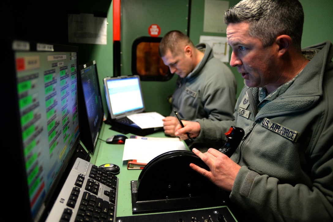 """U.S. Air Force Tech. Sgt. Robert Taylor, propulsion mechanic with the 177th Fighter Wing of the New Jersey Air National Guard, controls the throttle of an F-16C+ Fighting Falcon engine, while Master Sgt. Andre Lazaro, engine test cell supervisor, reviews engine telemetry data point printouts during testing at the propulsion shop's engine test facility, located at the Atlantic City Air National Guard Base in Egg Harbor Township, N.J. on Jan. 31, 2017. The facility, also known as the """"Hush House"""", is a multi-function building that can be used to perform diagnostic, troubleshooting and follow-on maintenance testing of the General Electric F110-GE-100 turbofan, which produces close to 29,000 pounds of static thrust in afterburner and can propel the Fighting Falcon to approximately twice the speed of sound. (U.S. Air National Guard photo by Master Sgt. Andrew J. Moseley/Released)"""