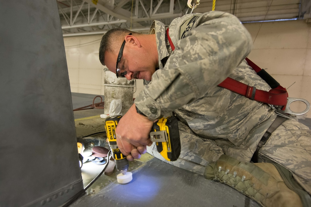 U.S. Air Force Master Sgt. Brent Proffitt, a sheet metal mechanic assigned to the 139th Maintenance Squadron, Missouri Air National Guard, sands down sheet metal on a C-130 Hercules aircraft at Rosecrans Air National Guard Base, St. Joseph, Mo., Feb. 8, 2017. Proffitt was assisting with aircraft maintenance that required the removal of the vertical stabilizer, or tail, of the aircraft. (U.S. Air National Guard photo by Master Sgt. Michael Crane)