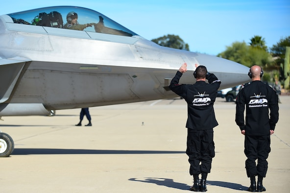 U.S. Air Force F-22 Raptor Demonstration Team crew chiefs, signal to an F-22 Raptor before take-off at the 2017 Heritage Flight Training and Certification Course at Davis-Monthan Air Force Base, Ariz., Feb. 9, 2017. The Demonstration Team assisted with more than 6 launches of the aircraft during the training and certification course. (U.S. Air Force photo by Senior Airman Kimberly Nagle)