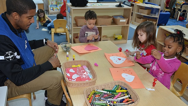 Derrhyl Duncan, a teacher in the four-year-old classroom of the Bettye Ackerman-Cobb Child Development Center, located on Defense Supply Center Richmond, Virginia, works with Eric Singleton, Kelly Bales, Kinsley Jackson (pink shirt) to make valentine cards Feb. 2, 2017 for veterans at the Hunter Holmes McGuire Veterans Medical Center as part of the VA's annual Sault to Veterans.