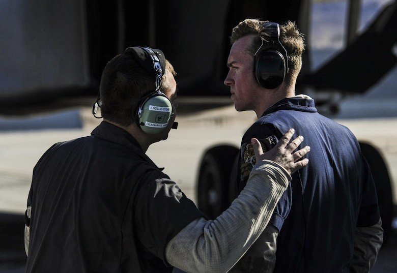 Staff Sgt. Justin Hollis and Senior Airman Jacob Widtmannheiser, crew chiefs assigned to the 28th Aircraft Maintenance Squadron, Ellsworth Air Force Base, S.D., talk as a B-1B Lancer prepares to takeoff during Red Flag 17-1 on Nellis Air Force Base, Nev., Jan. 27, 2017. All four branches of the U.S. military and air forces from allied nations participate in Red Flag in order to familiarize forces that will work together in future operations. (U.S. Air Force photo by Airman 1st Class Kevin Tanenbaum/Released)