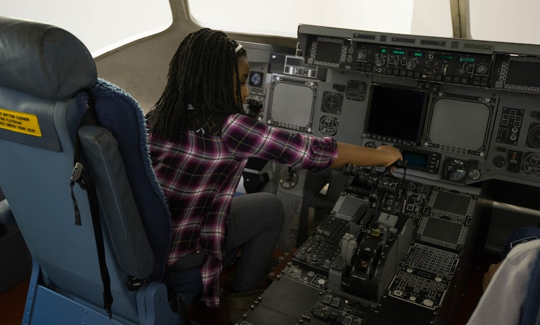 Kyla Palmer, 9, engages the controls of a mock up of a C-17 Globemaster III Feb. 11, 2017, on Joint Base Lewis-McChord, Wash. Palmer is a member of the Red-Tailed Hawks Flying Club, a non-profit youth organization chartered by the Black Pilots of America. (U.S. Air Force photo by David L. Yost)