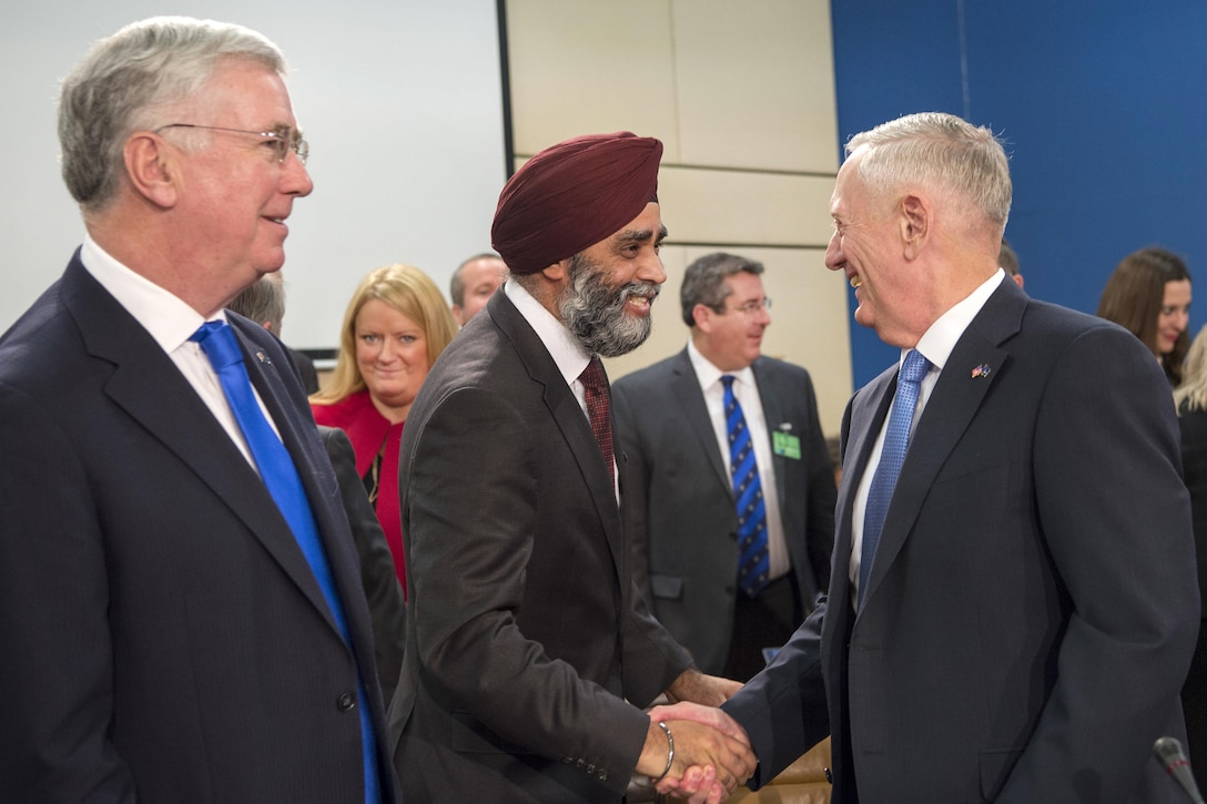Defense Secretary Jim Mattis exchanges greetings with Canadian Defense Minister Harjit Sajjan.