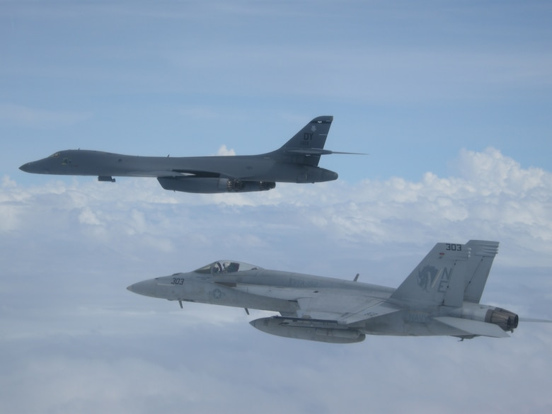 "A B-1B Lancer from Andersen Air Force Base in Guam and a F/A-18E Super Hornet from the ""Golden Dragons"" of Strike Squadron (VFA) 192 fly over aircraft carrier USS Carl Vinson (CVN 70) as it transits the Philippine Sea. The B-1s are deployed in support of U.S. Pacific Command's Continuous Bomber Presence mission. In place since 2004, the CBP missions are conducted by U.S. Air Force bombers such as the B-1, B-52 Stratofortress and B-2 Spirit in order to provide non-stop stability and security in the Indo-Asia-Pacific region. The Carl Vinson Strike Group is on a regularly scheduled Western Pacific deployment as part of the U.S. Pacific Fleet-led initiative to extend the command and control functions of U.S. 3rd Fleet. U.S. Navy aircraft carrier strike groups have patrolled the Indo-Asia-Pacific regularly and routinely for more than 70 years. (U.S. Navy photo by Lt. Robert Nordlund)"